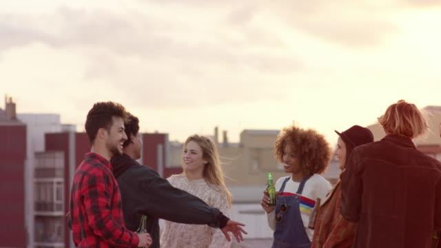multi-ethnic friends dancing while enjoying beer - terrazza video stock e b–roll