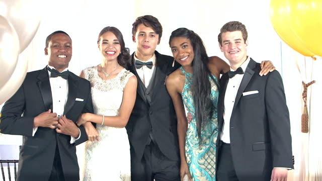 Multi-ethnic friends dressed for prom posing for photos video