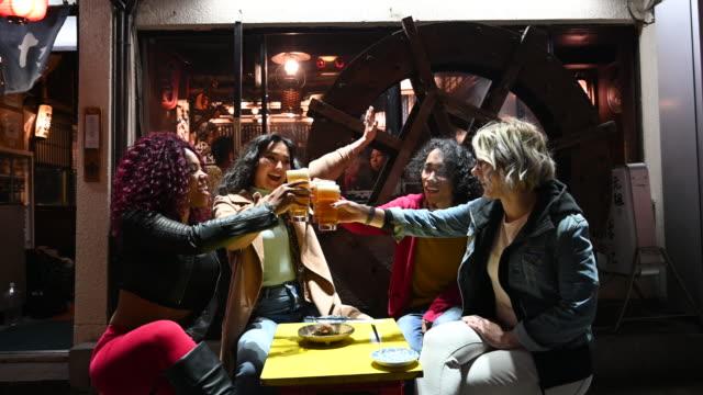 多民族の友人が日本の居酒屋で飲み物を楽しむ - 飲み会点の映像素材/bロール