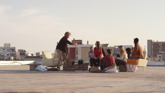 multi-ethnic friends enjoying beer on terrace - terrazza video stock e b–roll