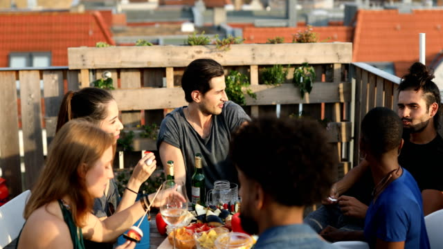 Multi-ethnic friends enjoying food and drink Handheld shot of friends enjoying food and drink while talking at rooftop. Multi-ethnic people are at reunion barbecue party. They are sitting at building terrace. mid adult stock videos & royalty-free footage