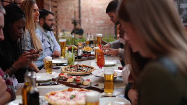 Multi-ethnic friends having fun time together at outdoor restaurant