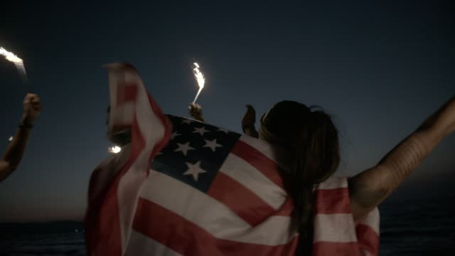 multi-ethnic friends partying on beach with sparklers and american flag - giorno dell'indipendenza video stock e b–roll