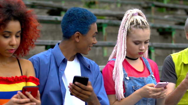 Multi-ethnic friends scrolling social networks, blue-haired guy sharing app news