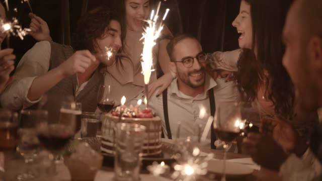 Multi-ethnic friends singing and celebrating birthday at rustic dinner party Multi-ethnic friends singing and celebrating man's birthday with sparklers and birthday cake at dinner party happy birthday stock videos & royalty-free footage