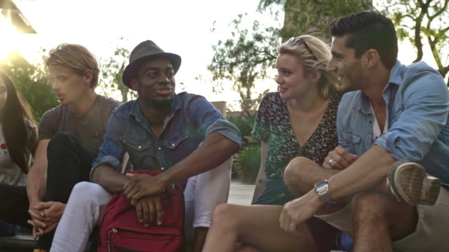 Multi-ethnic friends talking while sitting in city at sunset