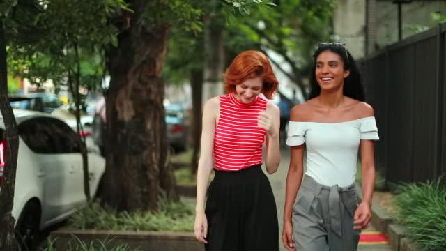 Multi-ethnic girlfriends walking in city sidewalk