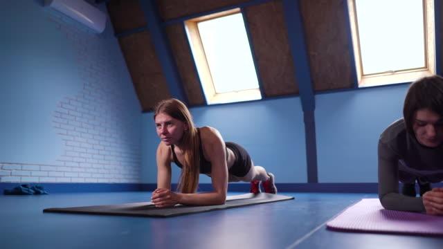 Multiethnic girls standing in plank in gym