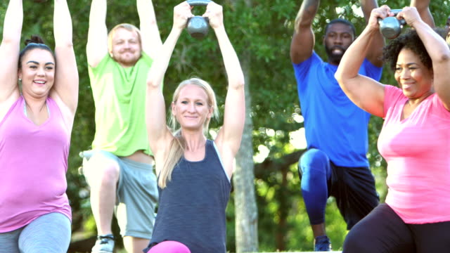 Multi-ethnic group in exercise class lifting kettlebells video
