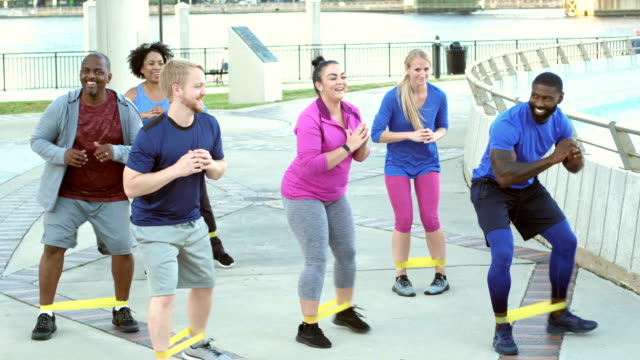 Multi-ethnic group in exercise class, resistance bands video