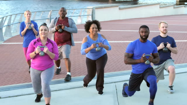 Multi-ethnic group in exercise class with kettlebells video