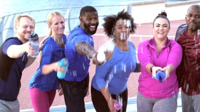 Multi-ethnic group in exercise class with water bottles video