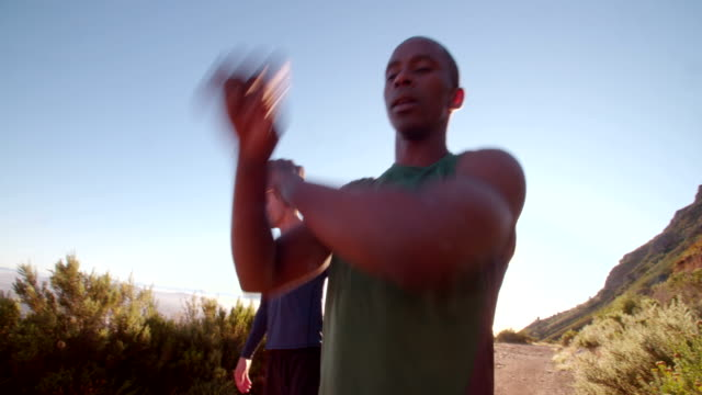 Multi-ethnic group of athletes doing hamstring stretch exercise outside video