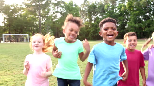 multi-ethnic group of boys and girls jumping in park - fianco a fianco video stock e b–roll