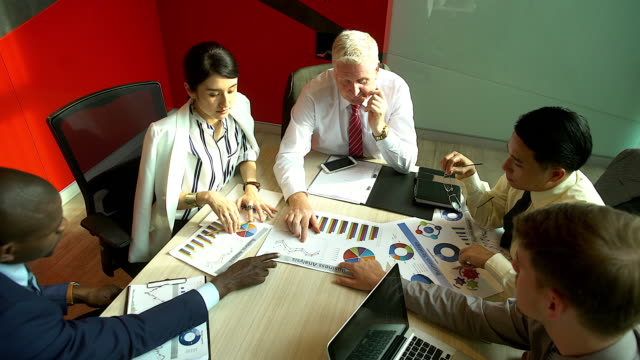 multi-ethnic group of businesspeople analyzing graphs and business document.graph document on the table. - direttrice video stock e b–roll