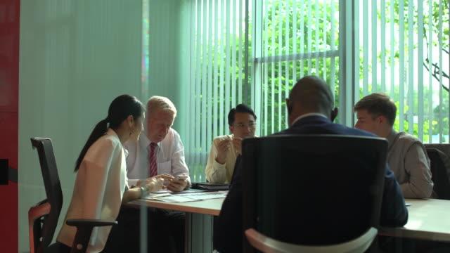 分析グラフやビジネス ドキュメントの実業家の多民族のグループ。テーブルの上のグラフ ドキュメント。 - ビジネスマン 日本人点の映像素材/bロール