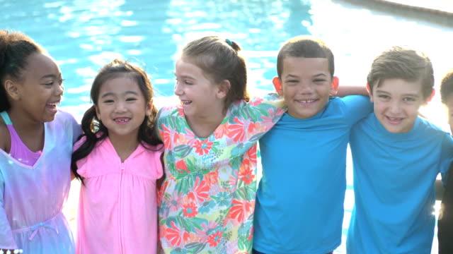 multi-ethnic group of children by swimming pool - fianco a fianco video stock e b–roll