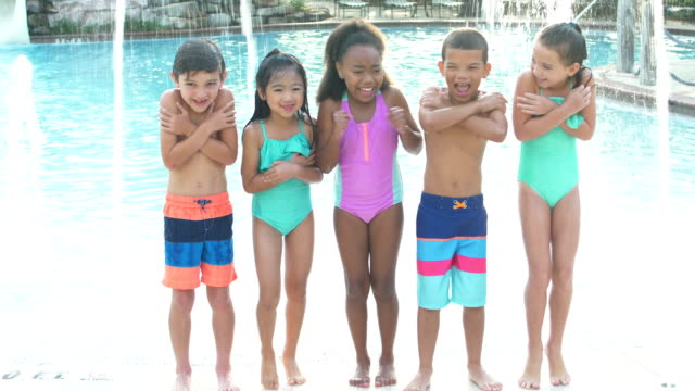 Multi-ethnic group of children by swimming pool A multi-ethnic group of five boys and girls standing on a swimming pool deck side by side. They are 6 to 9 years old. The two boys three girls are smiling at the camera, arms crossed, shivering. shivering stock videos & royalty-free footage