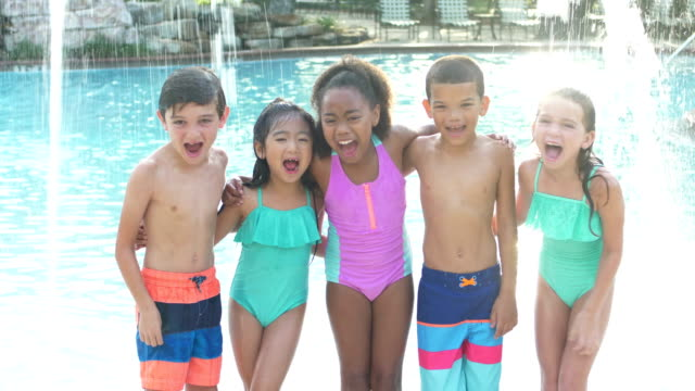 Multi-ethnic group of children by swimming pool A multi-ethnic group of five boys and girls standing on a swimming pool deck side by side. They are 6 to 9 years old. The two boys three girls are smiling, laughing and shouting at the camera, arms around each other. shivering stock videos & royalty-free footage
