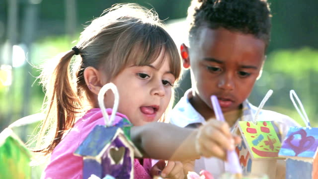 Multi-ethnic group of children painting birdhouses video