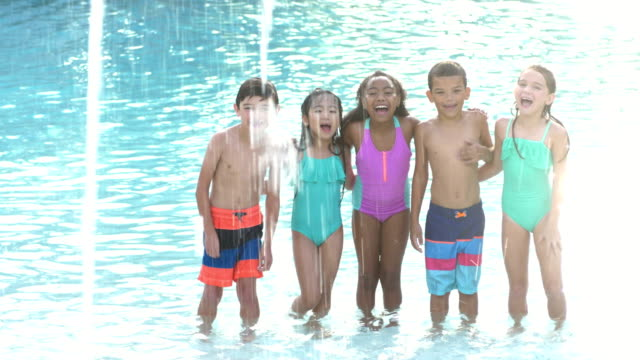 Multi-ethnic group of children standing in swimming pool