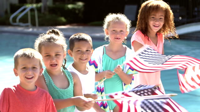 Multi-ethnic group of children waving American flags video