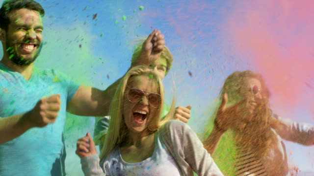 vídeos de stock e filmes b-roll de multi-ethnic group of  diverse young people throw colorful powder at each other in celebration of holi festival. they have enormous fun on this sunny day. - holi