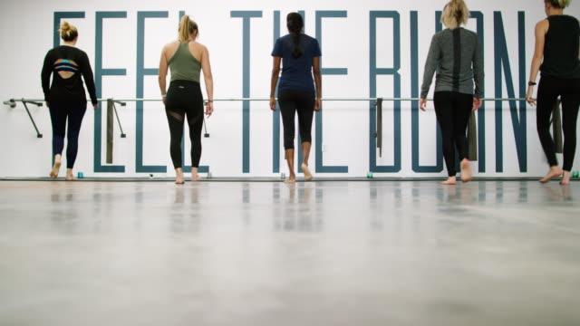ett multietniskt grupp fem kvinnor i tjugoårsåldern promenad till en balett barre och börja stretching i en motion studio - balettstång bildbanksvideor och videomaterial från bakom kulisserna