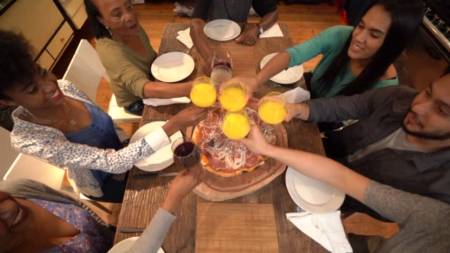 Multi-ethnic group of friends and family at celebratory toast on a dinner party