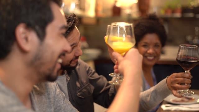 vídeos de stock, filmes e b-roll de multi-étnica grupo de amigos e família no brinde de comemoração em um jantar - brasileiro pardo