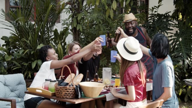 vidéos et rushes de groupe d'amis multi-ethniques sur profiter d'une fête de barbecue - man drinking terrace