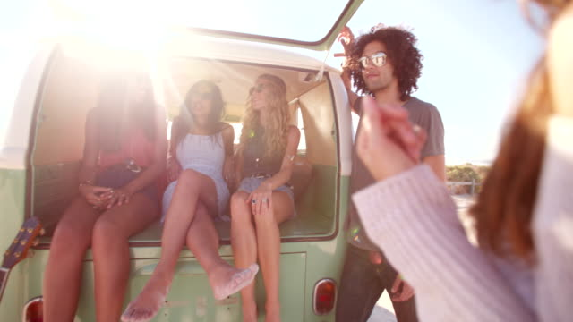 Multi-Ethnic group of friends sit in back of open retro van video
