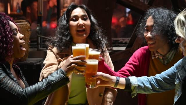 友人の多民族グループは一緒にビールのグラスを乾杯 - 飲み会点の映像素材/bロール