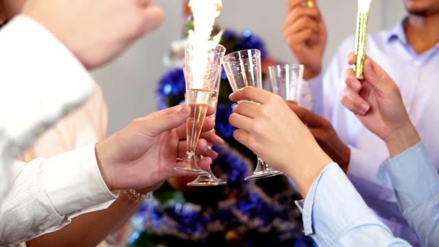 multiethnische gruppe glücklich büroangestellte klirren der gläser mit sekt während bengal-lichter und tragen weihnachtsmützen feiert weihnachten und neujahr. slowmotion aufnahme - champagner toasts stock-videos und b-roll-filmmaterial