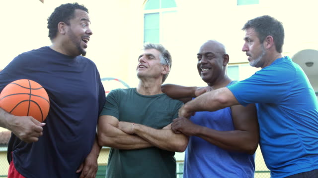 multi-ethnic group of middle aged men playing basketball - fianco a fianco video stock e b–roll