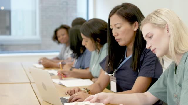 sınıfta hemşirelik öğrencilerinin çok ırklı bir grup - cerrahi önlük stok videoları ve detay görüntü çekimi