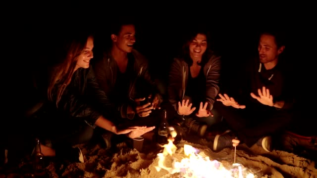 Multiethnic group of people sitting by the bonfire at the beach and warming up their hands in the evening, talking and having fun together - video
