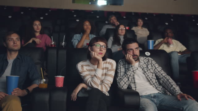 Multiethnic group of people watching movie in cinema holding drinks and food Multiethnic group of people viewers watching movie in cinema holding drinks and food sitting in seats wearing casual clothing. Youth culture and lifestyle concept. lounge chair stock videos & royalty-free footage