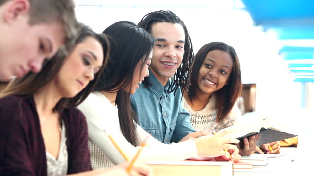 Multi-ethnic group of students studying in library A multi-ethnic group of high school or university students studying in the library. Three of them are working together talking and looking at a textbook. textbook stock videos & royalty-free footage