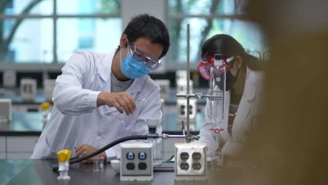 Multi-ethnic group of students working in lab wearing face masks Group of chemistry students working in the laboratory conducting experiments while wearing lab coats and protective face masks due to the new COVID-19 school regulations. student life stock videos & royalty-free footage