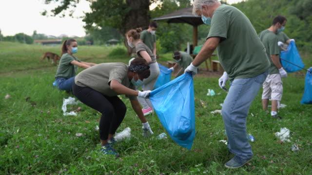 vidéos et rushes de groupe multiethnique de bénévoles nettoyant un parc public pendant la pandémie de coronavirus - assistant