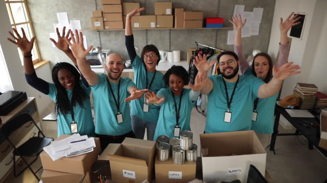 Multi-ethnic group of volunteers waving and smiling Group of multi-ethnic volunteers standing in front of desk with humanitarian aid, waving and smiling giving tuesday stock videos & royalty-free footage