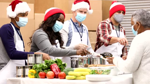 Multi-ethnic group of volunteers work at soup kitchen at Christmas. Multi-ethnic, mixed age group of volunteers work together at food bank, soup kitchen during Christmas season.  They serve food to needy people in their community at holiday times. Face masks. giving tuesday stock videos & royalty-free footage