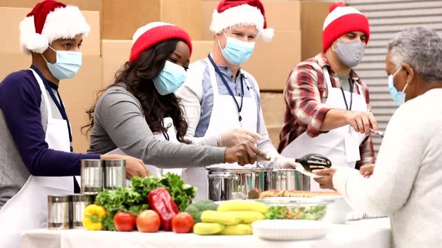 다민족 자원봉사자들이 크리스마스에 수프 주방에서 일하고 있습니다. - giving tuesday 스톡 비디오 및 b-롤 화면