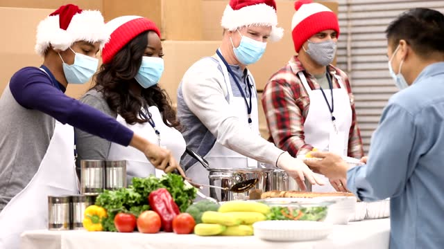 Multi-ethnic group of volunteers work at soup kitchen at Christmas.