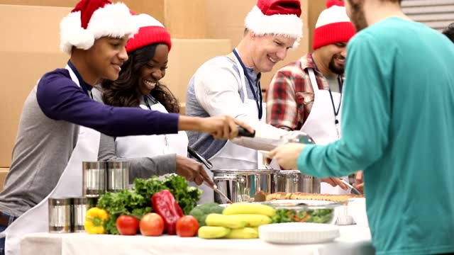 Multi-ethnic group of volunteers work at soup kitchen at Christmas. Multi-ethnic, mixed age group of volunteers work together at food bank, soup kitchen during Christmas season.  They serve food to needy people in their community at holiday times. food drive stock videos & royalty-free footage