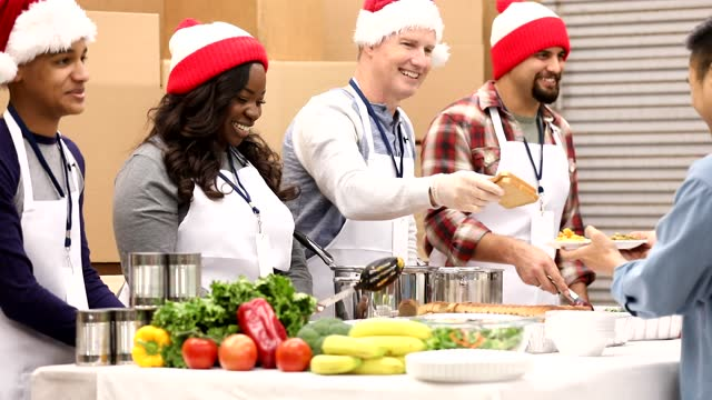 Multi-ethnic group of volunteers work at soup kitchen at Christmas. Multi-ethnic, mixed age group of volunteers work together at food bank, soup kitchen during Christmas season.  They serve food to needy people in their community at holiday times. giving tuesday stock videos & royalty-free footage
