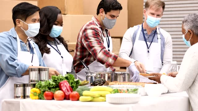 Multi-ethnic group of volunteers work at soup kitchen. Multi-ethnic, mixed age group of volunteers work together at food bank, soup kitchen.  They serve food to needy people in their community. Face masks. giving tuesday stock videos & royalty-free footage