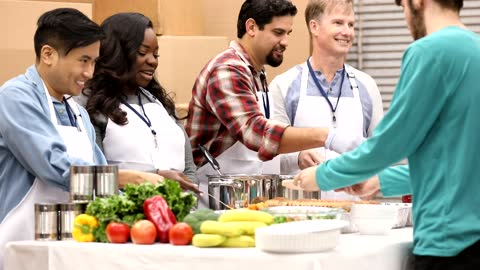 Multi-ethnic group of volunteers work at soup kitchen. Multi-ethnic, mixed age group of volunteers work together at food bank, soup kitchen.  They serve food to needy people in their community. giving tuesday stock videos & royalty-free footage