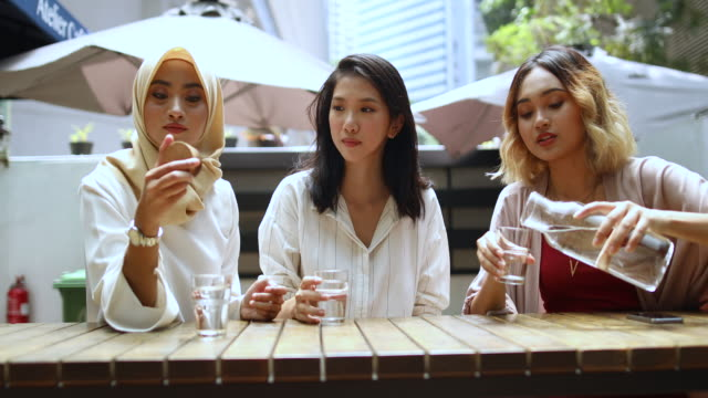 multi-ethnic group of women drinking water in the cafe - acqua potabile video stock e b–roll